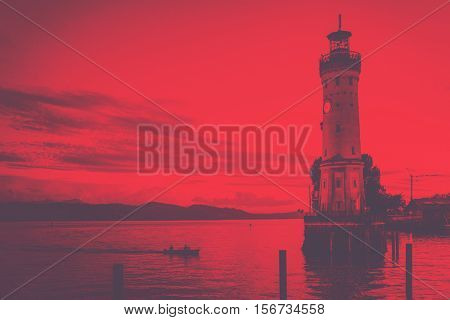 Small boat approaching the Lindau lighthouse at sunset silhouetted against the reflection of the orange sky on the water, Lake Constance, Bavaria, Germany