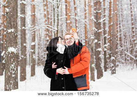 Couple taking self portrait with smart phone in winter park. Beautiful young couple selfie.