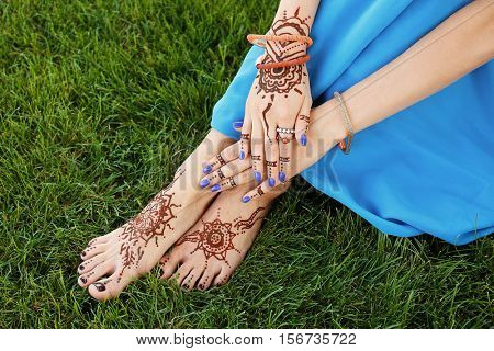 Female legs and hands with henna tattoo on green grass background