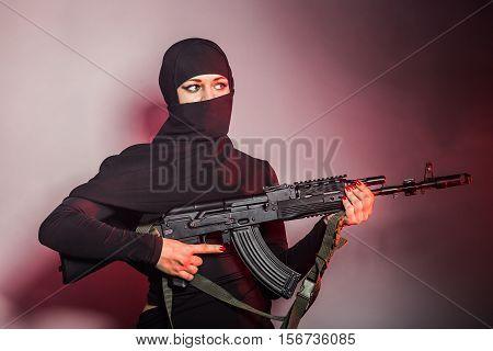 woman with machine gun. Armed female. Terrorist woman holding a submachine gun. Woman in black with gun