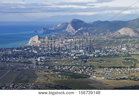 Panorama of the small resort town of Sudak from the top of the mountain Ai-George (or Saint George). Crimea September.