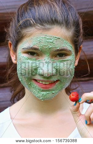 teen girl with natural blue clay face mask and strawberry on the outdoor country summer background smiling