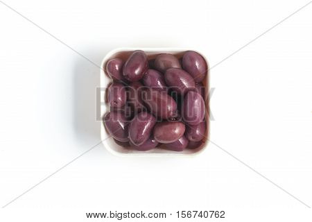 Black olives into a bowl isoalted on white background