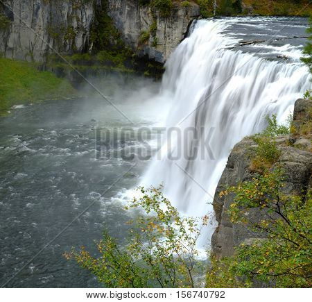 Mesa Falls Water Falls and Flowing River in Cayon Lush Green Foliage Powerful Water