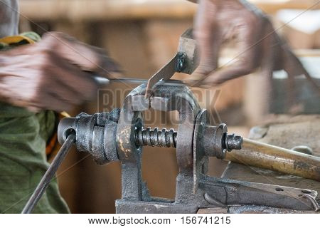 Dindigul India - October 23 2013: Closeup of hands moving fast back and forth while abrading rubbing filing a piece of metal lock held in a vise. The movement is visible.