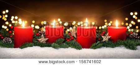 Festive studio shot of elegant advent decoration with fir branches on snow and four burning red candles dark wood background with bokeh lights