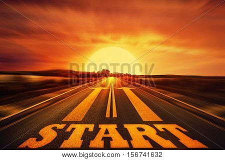Word Start written on an asphalt road and two arrows as motivation. Long way ahead as a concept of start straight for business.
