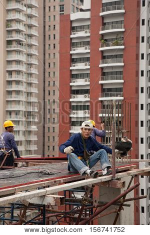 Bangkok, Thailand - November 10, 2008 :  Workers on a building site in Bangkok. Salaries are very low for a dangerous and tiring work. Most workers come from the north east of Thailand, Cambodia and Myanmar.