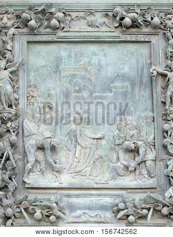 PISA, ITALY - JUNE 06, 2015: The payment of the tribute, sculpture work from Giambologna's school, left portal panel of the Cathedral St. Mary of the Assumption in Pisa, Italy on June 06, 2015