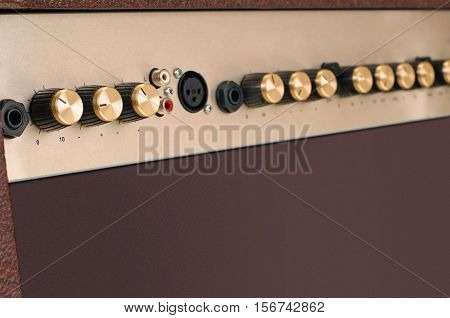 adjustment knobs and connection entrance on brown Guitar Amplifier