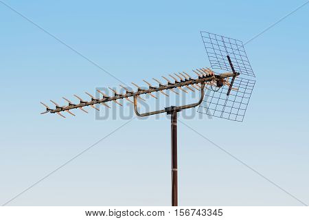 old TV antenna isolated on blue sky background