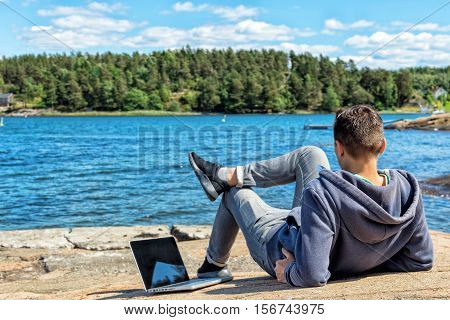 Freelancer man with laptop on colorful beach of island