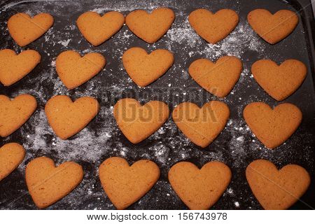 A group of brown gingerbread hearts on a baking sheet.