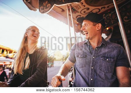 Laughing young friends riding on carousel in amusement park. Smiling couple on carousel ride.
