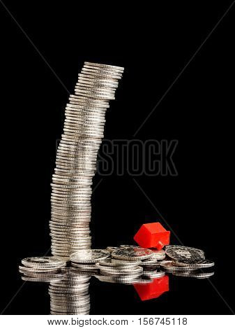A tall stack of coins has failed togather with a red small plastic house.