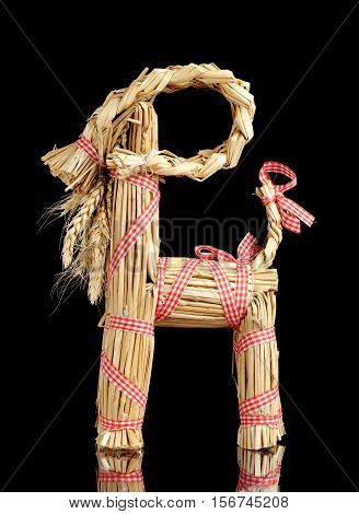 A traditional Swedish Christmas goat (julbock) made of straw on black background.