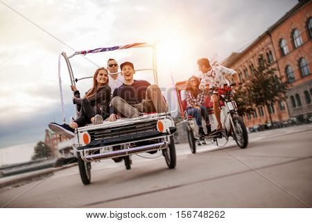 Happy young friends going on tricycle ride through the city. Teenagers sitting on tricycles on road.