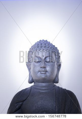 Oriental buddha statuette figure isolated on plain background.