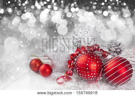 Red Christmas balls over sparkling holiday background. Magic holiday lights. Merry Christmas and a Happy New Year