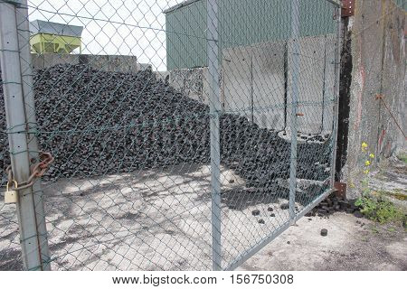 Heap of coal briquets behind a wire mesh gate.