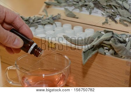 Person gives several drops of medicine into a liquid - close-up