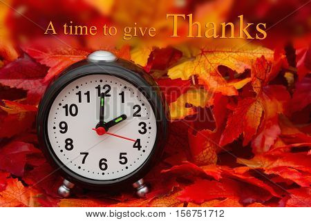 Time to give thanks message Some fall leaves and black and white alarm clock with text A Time to give thanks