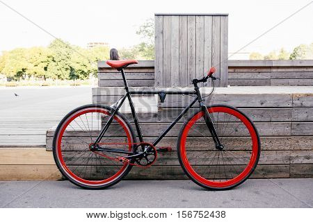 Red bycicle parked near wooden bench in park