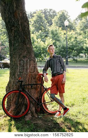 Hipster with red bycicle and tattoo on leg in park
