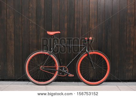 Red bycicle parked near brown wall side view