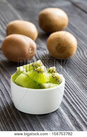 kiwi on a wooden background. in the foreground sliced kiwi. close-up