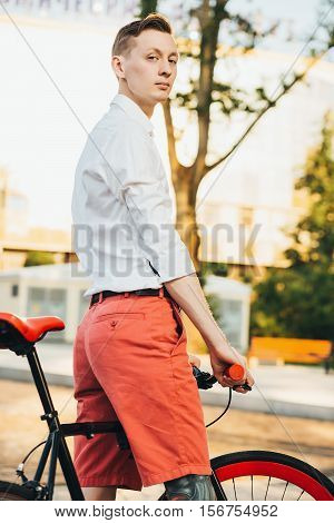 Hipster with red bycicle and tattoo on leg.