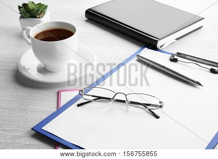 Glasses, clipboard and cup of coffee on wooden table. Healthy eyes concept