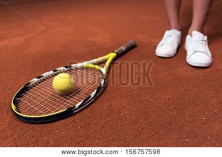 Nessecary equipment. Close up of tennis racket and tennis ball lying on the clay surface of tennis court
