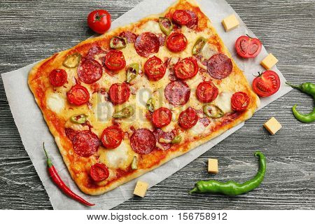 Delicious pizza with ingredients on wooden background