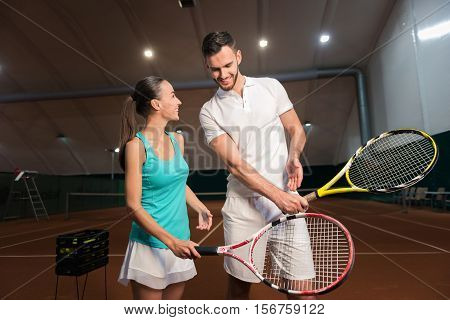 Lead an active lifestyle. Cheerful delighted friends smiling and holding rackets while going to play tennis in an indoor tennis court