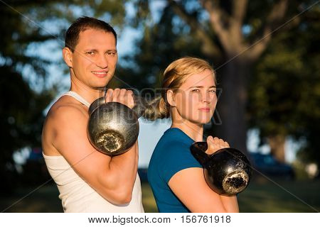 Man and woman couple holding heavy kettlebell weights in outdoor park