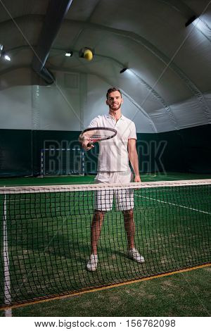 Get ready. Positive delighted professional tennis player holding racket and playing with ball while going to have a set
