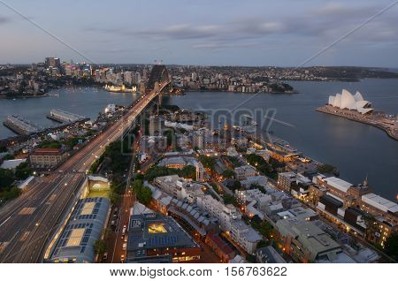 SYDNEY AUS - OCT 20 2016:Aerial urban landscape view of Sydney Harbour with Sydney Harbour Bridge the Opera House Circular Quay and The Rocks with North Sydney in the background at dusk in New South Wales Australia.