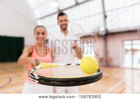 Brighten your life. Selective focus of tennis ball lying on the racket while positive professional female player holding it