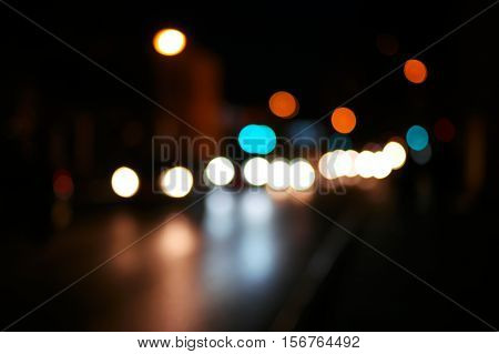 Night road city blur bokeh shot. Blurred street with carlights in night time. Defocused urban scene. Toned color shot.