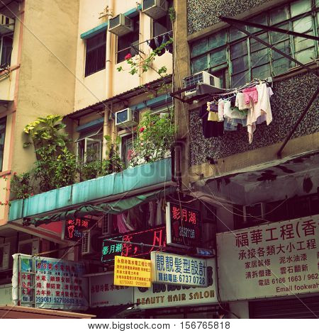 Hong Kong - October 2016: Typical Kowloon house with hanging clothes, flowers and signboards. Retro look.
