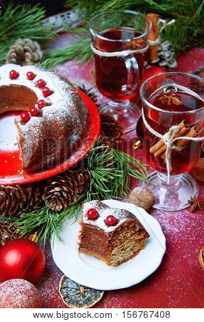 Piece of christmas pudding cake on white saucer decorated with berries sprinkled with sugar powder. Traditional christmal food.