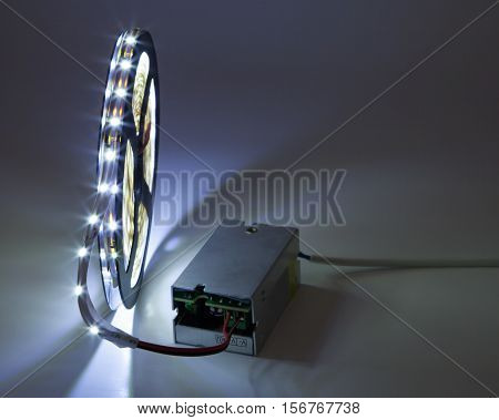 Coil of luminous LED strip light connected to voltage transformer.