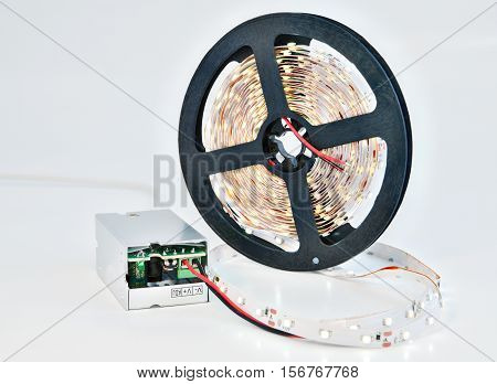Illuminated LED diodes on a reel tape with adapter voltage converter.