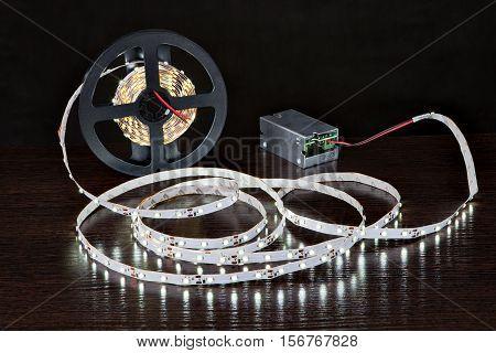 Shining LED Strip Light on a reel near power unit on a black background.