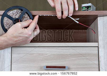 Using LED strip light lighting for indoor furniture close-up human hands glued tape on board.