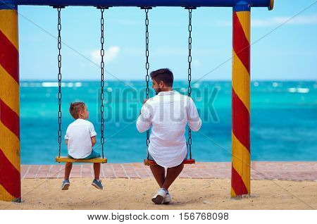 Father And Son Talking On Swings On The Beach