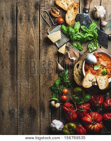 Homemade Italian roasted tomato and garlic soup in bowl with basil and Parmesan cheese over old rustic wood background, top view, copy space, verticall composition