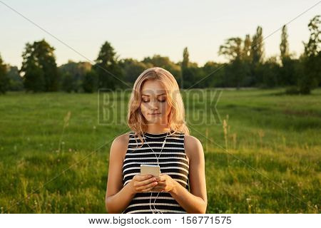 Portrait of fair-haired girl with her mobile phone and earphones on a green background