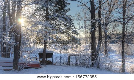 Winter sunrise morning in a cottage back woods. Wintry fresh fallen snow is revealed as the sun comes up on cold, wooded cottage lake.  Upside down boat waits for the next season.